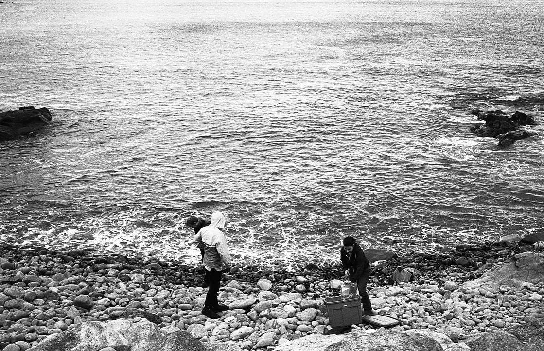 Black and white photograph of two figures on a rocky shore dwarfed by a huge ocean above them.